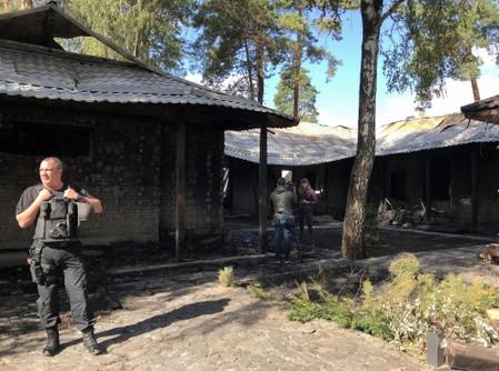A law enforcement officer stands at a site of a burnt house, which is reportedly owned by former Governor of the Ukrainian Central Bank Valeria Gontareva, in Kiev