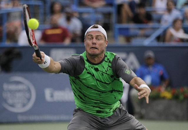 Lleyton Hewitt, of Australia, reaches for the ball during a game against Milos Raonic, of Canada, at the Citi Open tennis tournament, Thursday, July 31, 2014, in Washington. (AP Photo/Luis M. Alvarez)