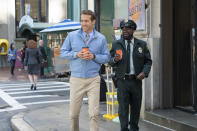 """This image released by 20th Century Studios shows Ryan Reynolds, center, and Lil Rel Howery in a scene from """"Free Guy."""" (Alan Markfield/20th Century Studios via AP)"""