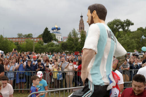 People gather around a sculpture cake to mark Lionel Messi's birthday near Argentina training camp base at the 2018 World Cup in Bronnitsy, Russia, Sunday, June 24, 2018. Wth a cake sculpture and a music festival the town of Bronnitsy celebrated the striker's 31st birthday.(AP Photo/Ricardo Mazalan)