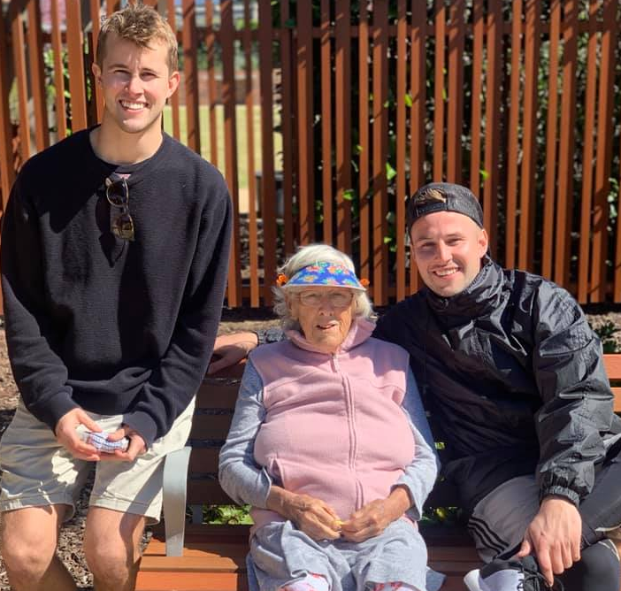 Sydney brothers Logan (right) and Dane Hopper (left) with their grandmother sitting on a park bench smiling.