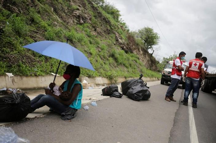 A migrant rests with her baby as migrants, which are stranded in Honduras after borders were closed due to the coronavirus disease (COVID-19) outbreak, rest while trekking northward in an attempt to reach the United States, in Choluteca