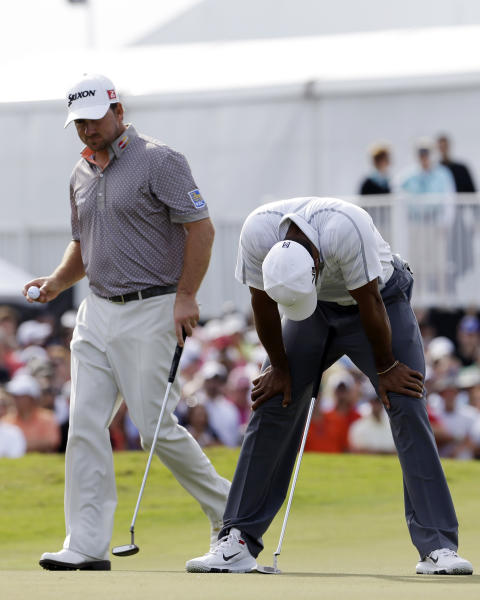 Tiger Woods bows his head in frustration after missing a putt for birdie on the ninth green as Graeme McDowell of Northern Ireland, gets ready to place his ball during the third round of the Cadillac Championship golf tournament Saturday, March 9, 2013, in Doral, Fla. (AP Photo/Alan Diaz)