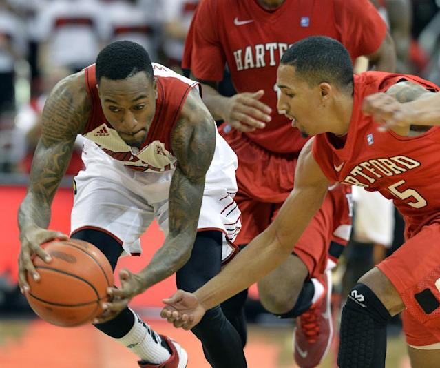 Louisville's Kevin Ware, left, battles Hartford's Yolonzo Moore II for a loose ball during the second half of their NCAA college basketball game Nov. 19, 2013, in Louisville, Ky. Louisville defeated Hartford 87-48. (AP Photo/Timothy D. Easley)