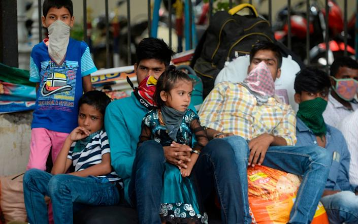 Stranded migrant workers wait to board a train in India as the Government eases a nationwide lockdown - AFP