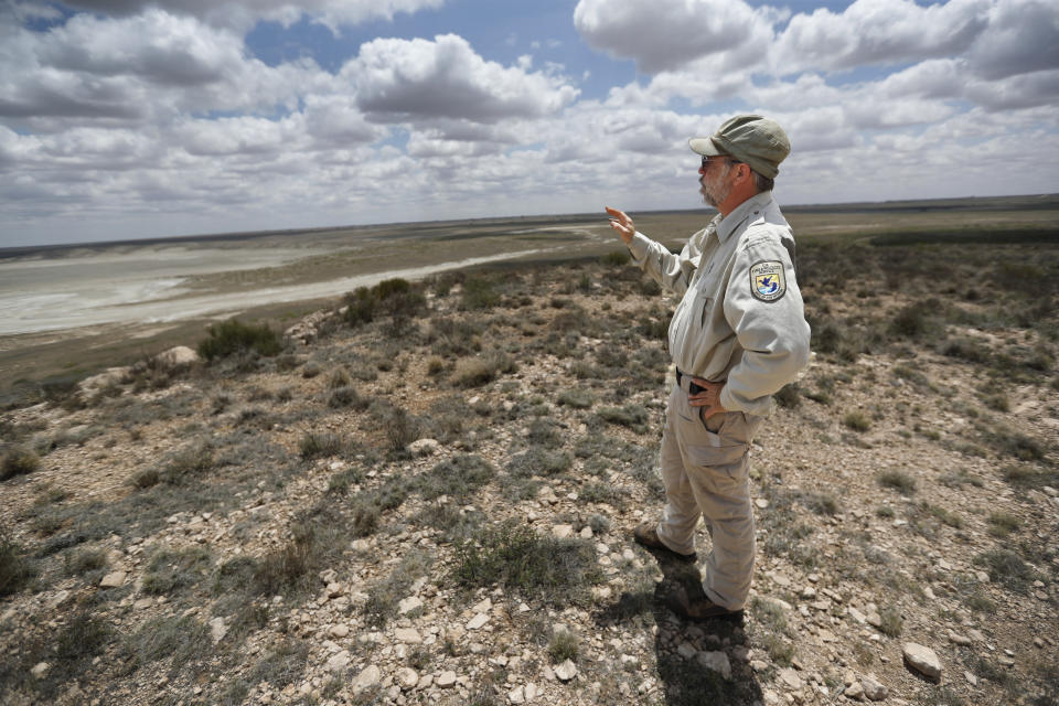Biologist Jude Smith stands on a bluff overlooking an empty saline lake at the Muleshoe National Wildlife Refuge outside Muleshoe, Tex., on Tuesday, May 18, 2021. The lake is fed by the Ogallala Aquifer, which has been become increasingly dry because of irrigation and drought. (AP Photo/Mark Rogers)