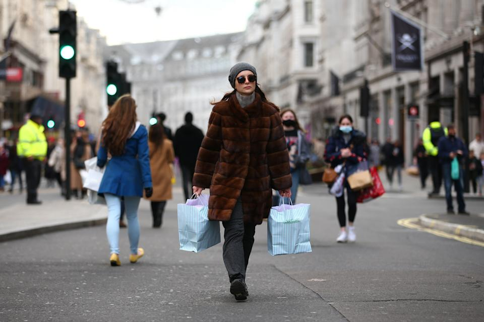 A woman carries bags of shopping along Regent Street in London, England. Photo: David Cliff/NurPhoto via Getty Images
