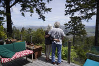 Gordon Bennett and his wife Kate Carolan stand on the deck outside their home and look at the view, Friday, April 30, 2021, in Inverness, Calif. The couple, who were victims of Bernard Madoff and forced to sell their home, now rent it back from someone they know who purchased it. More than 12 years after Madoff confessed to running the biggest financial fraud in Wall Street history, a team of lawyers is still at work on a sprawling effort to recover money for the thousands of victims of his scam. (AP Photo/Eric Risberg)