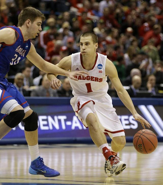 Wisconsin guard Ben Brust (1) drives against American center Tony Wroblicky (34) during the second half of a second-round game in the NCAA college basketball tournament Thursday, March 20, 2014, in Milwaukee. (AP Photo/Jeffrey Phelps)