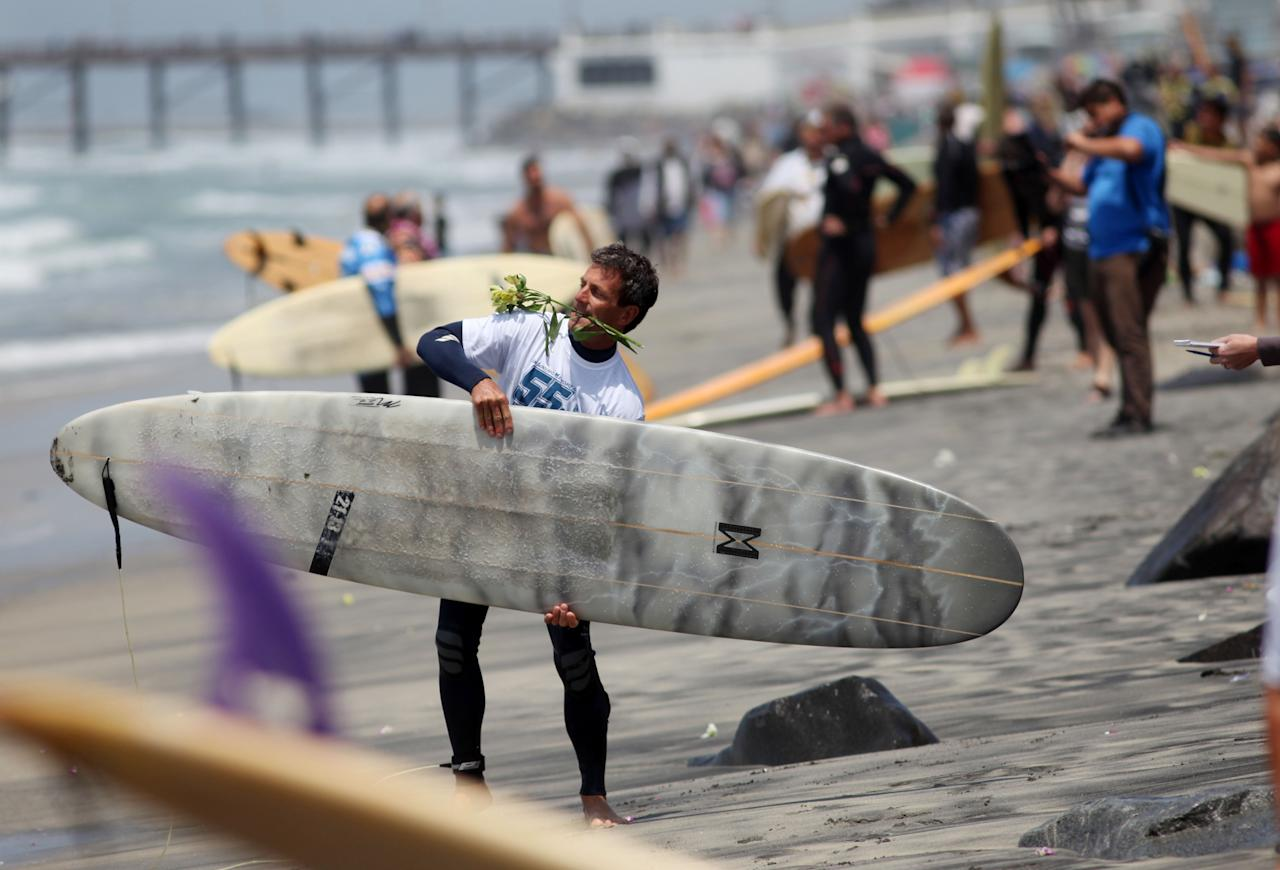 """OCEANSIDE, CA - MAY 6: Surfers prepare go into the surf for a ceremony during a """"paddle-out"""" in honor of NFL star Junior Seau on May 6, 2012 in Oceanside, California.  Seau, who played for various NFL teams including the San Diego Chargers, Miami Dolphins and New England Patriots was found dead in his home on May 2nd of an apparent suicide.  Family members have decided to donate his brain for research on links between concussions and possible depression. (Photo by Sandy Huffaker/Getty Images)"""