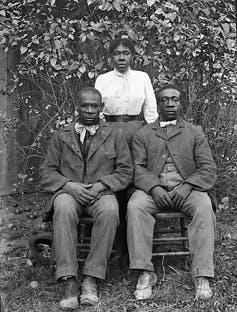 Two Black men seated in chairs while their sister stands behind them.