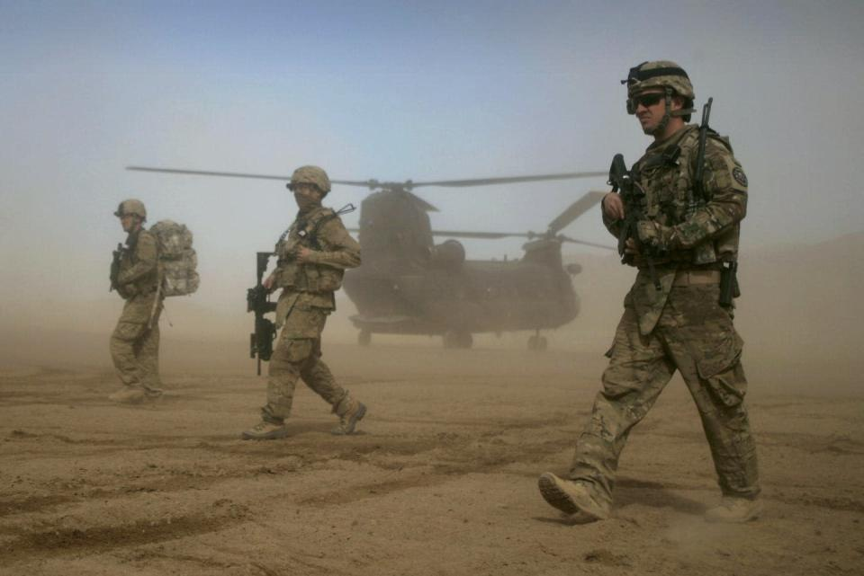 U.S. soldiers in combat gear walk through blowing sand with a helicopter behind them.