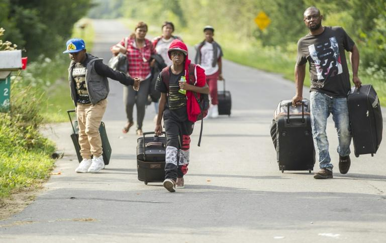 A group of asylum seekers prepare to cross into Canada from the United States