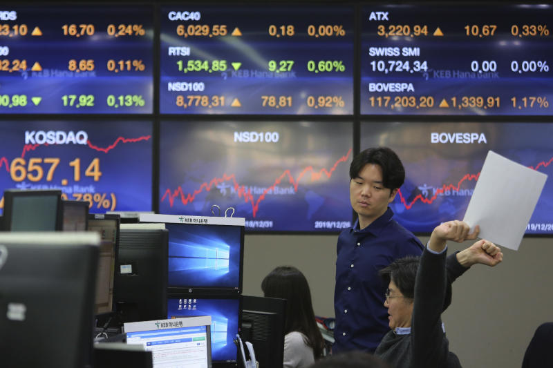 A currency trader stretches at the foreign exchange dealing room of the KEB Hana Bank headquarters in Seoul, South Korea, Friday, Dec. 27, 2019. Asian stocks followed Wall Street higher on Friday amid optimism U.S.-Chinese trade relations are improving. (AP Photo/Ahn Young-joon)