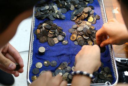 FILE PHOTO : Officers count coins that were removed from the stomach of Omsin, a 25 year old femal green sea turtle after a surgery at the Faculty of Veterinary Science, Chulalongkorn Universiry in Bangkok, Thailand, March 6, 2017. REUTERS/Athit Perawongmetha/File photo