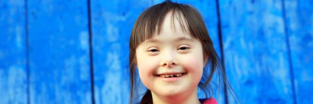 Girl with Down syndrome smiling. Blue wall in background.