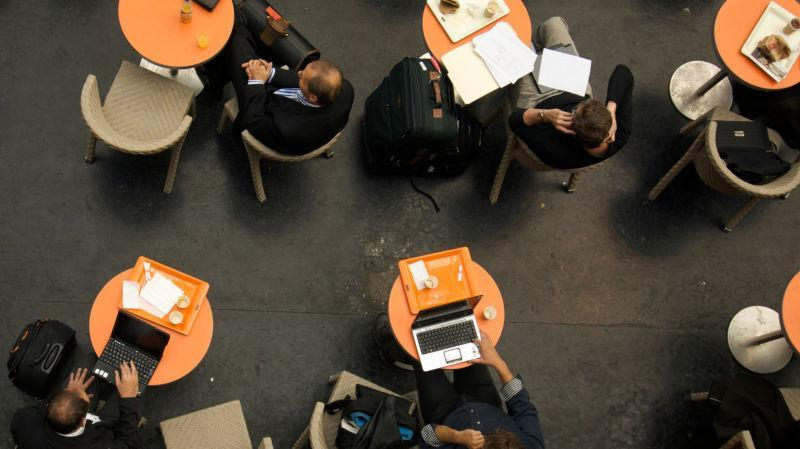 Customers and laptops in a coffee shop