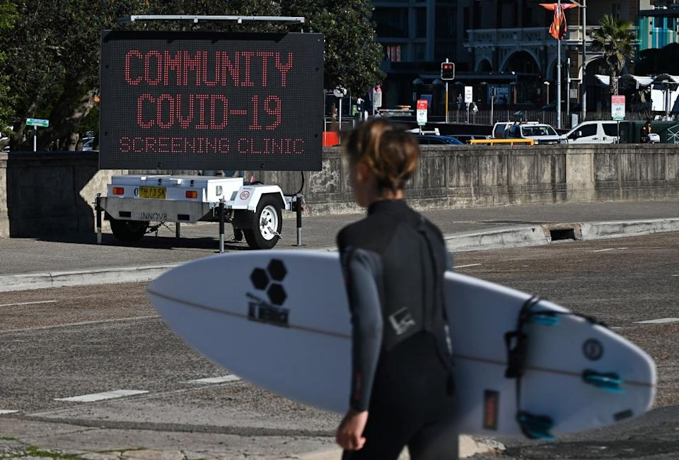 A surfer walks past a sign for a COVID-19 testing clinic at Bondi Beach in Sydney on the first full day of a two-week coronavirus lockdown to contain an outbreak of the highly contagious Delta variant.