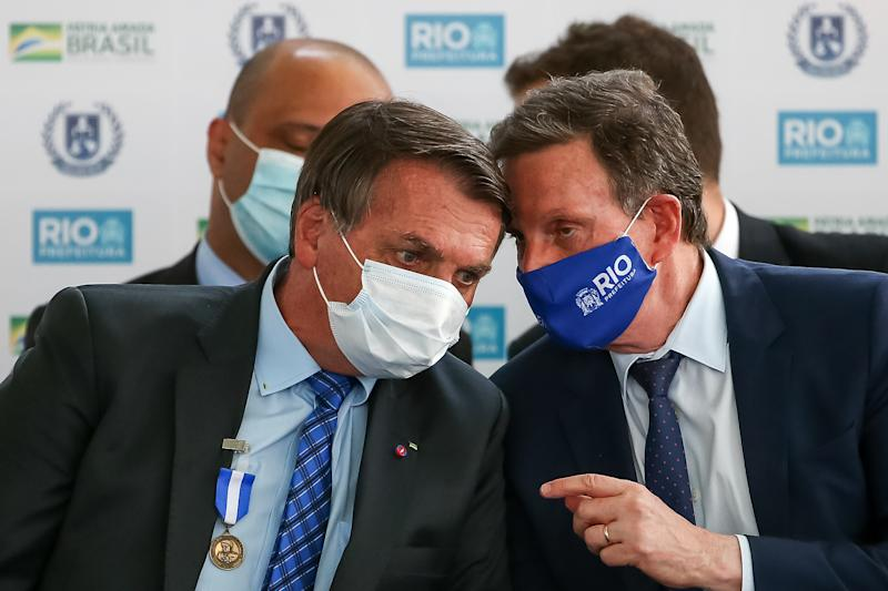 RIO DE JANEIRO, BRAZIL - AUGUST 14: President of Brazil Jair Bolsonaro (L) talks to the Mayor of Rio de Janeiro Marcelo Crivella (R) during the opening of the Escola Civico-Militar General Abreu on August 14, 2020 in Rio de Janeiro, Brazil. The civic-military school inaugurated by the city of Rio de Janeiro has a capacity for 500 students. Two other units will be added to the complex, which will be launched by the end of the year. Civic-military schools are non-militarized institutes with retired military agents as tutors, a model advocated by the government of Jair Bolsonaro. (Photo by Buda Mendes/Getty Images)