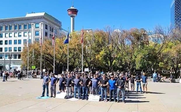 Images of a few dozen purported firefighters and police officers linking arms outside of City Hall circulated online after the demonstration on Tuesday, while videos showed others lining up to touch the Calgary Firefighters Civic Memorial. (@JaneQCitizen/Twitter - image credit)