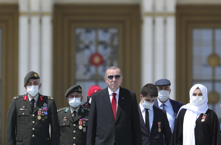 """Turkey's President Recep Tayyip Erdogan and family members of coup victims walk to place flowers by the """"Martyrs Monument"""" outside his presidential palace, in Ankara, Turkey, Wednesday, July 15, 2020. Turkey is marking the fourth anniversary of the July 15 failed coup attempt against the government, with prayers and other events remembering its victims.(Turkish Presidency via AP, Pool)"""