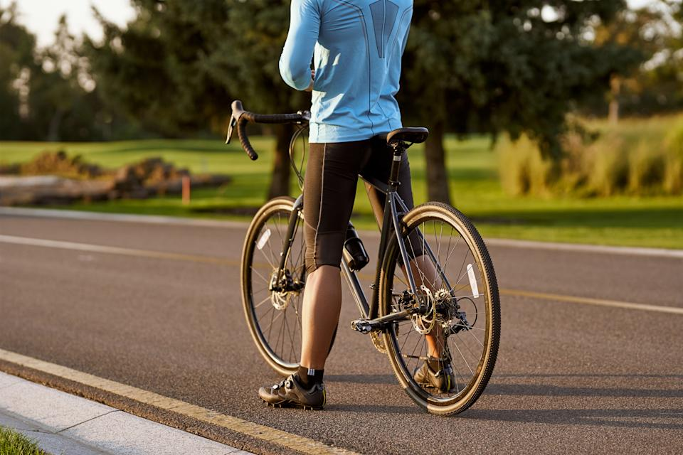 Rear view of athletic man in sportswear standing with bicycle on the road. Riding mountain road bike on a sunny summer day. Healthy active lifestyle and sport concept