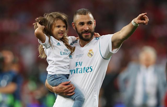 Soccer Football - Champions League Final - Real Madrid v Liverpool - NSC Olympic Stadium, Kiev, Ukraine - May 26, 2018 Real Madrid's Karim Benzema celebrates winning the Champions League with a child at the end of the match REUTERS/Hannah McKay