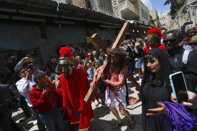 An actor carries a cross toward the Church of the Holy Sepulchre, traditionally believed to be the site of the crucifixion of Jesus Christ, during the Good Friday procession in Jerusalem's old city on April 19, 2019. (Ariel Schalit / ASSOCIATED PRESS)