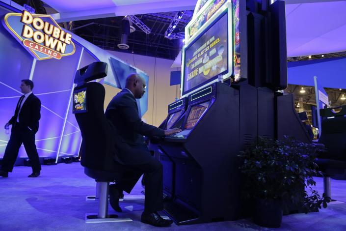 Excalibur hotel-casino slot shift manager, Bisrat Gemechu, plays the Little Green Men video game slot machine at the Global Gaming Expo, Wednesday, Sept. 25, 2013, in Las Vegas. One of two first-generation joystick-controlled gambling machines produced by IGT, the game broadcasts the gambler's performance on an overhead screen, and pays out points in cash. (AP Photo/Julie Jacobson)