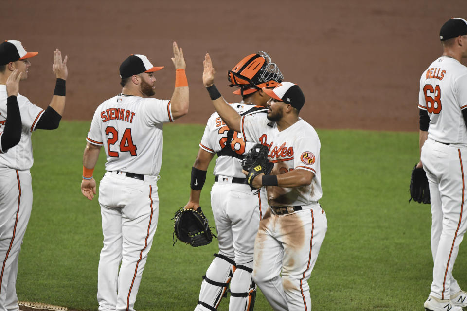 Baltimore Orioles congratulate one anoterh after defeating the Los Angeles Angels 10-6 in a baseball game Wednesday, Aug. 25, 2021, in Baltimore. (AP Photo/Terrance Williams)