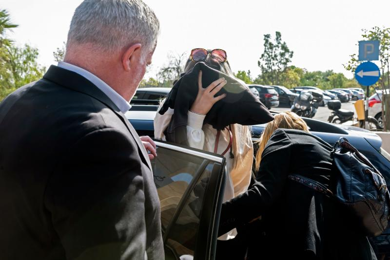 "A British teenager who accused seven Israelis of gang rape covers her face as she comes in the Larnaca District Court on November 01, 2019. - Initially, the Briton had alleged 12 Israelis raped her on July 17 at a hotel in the resort of Ayia Napa, a magnet for younger tourists attracted by its beaches and nightlife. The Israelis aged 15 to 18, several of whom had been detained, were released without charge after she was arrested on suspicion of ""making a false statement about an imaginary crime"", according to police. (Photo by Iakovos Hatzistavrou / AFP) (Photo by IAKOVOS HATZISTAVROU/AFP via Getty Images)"