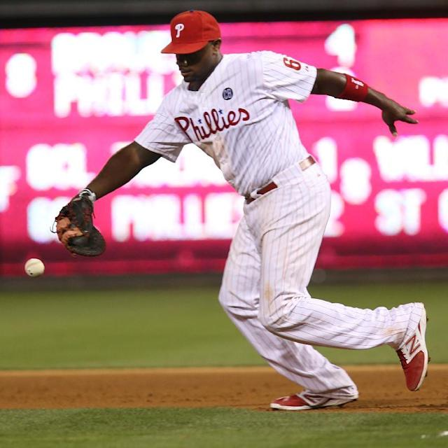 Philadelphia Phillies' Ryan Howard chases a grounder by Atlanta Braves' Tommy La Stella before throwing to pitcher Kyle Kendrick for the out at first in the eighth inning of a baseball game, Friday, June 27, 2014, in Philadelphia. Atlanta won 4-2. (AP Photo/Laurence Kesterson)
