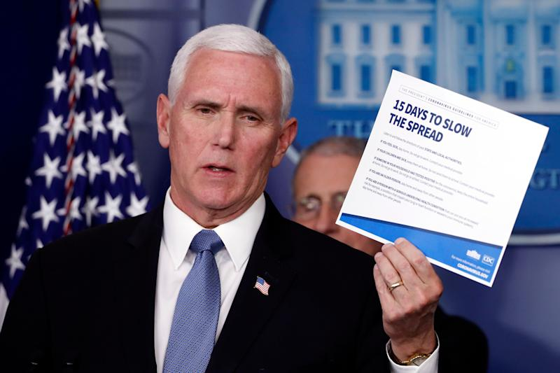 Vice President Mike Pence holds up a card about coronavirus prevention in the James Brady Briefing Room on March 24, 2020, in Washington.  (AP Photo/Alex Brandon)