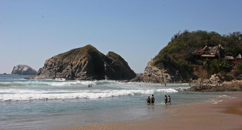 This Dec. 18, 2012 photo shows visitors bathing in the surf along the beach in Zipolite, Mexico. A sleepy town with one main street and no ATMs, Zipolite is one many tiny coastal pueblos that dot the Pacific in Mexico's Southern state of Oaxaca. (AP Photo/Jody Kurash)