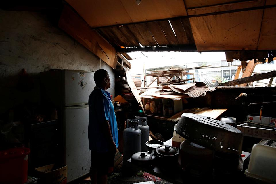 <p>A man looks through a damaged rooftop caused by Typhoon Nepartak at his house, in Taitung, Taiwan July 9, 2016. (Photo: Tyrone Siu/REUTERS) </p>