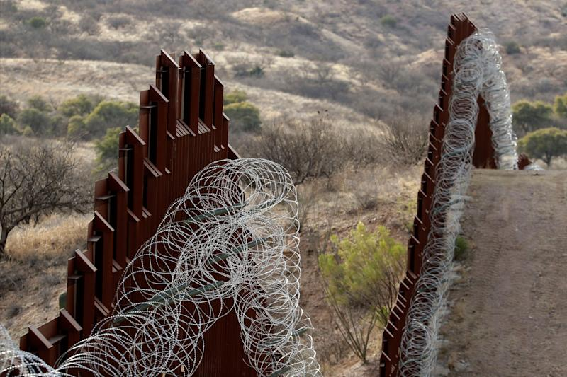 A razor-wire-covered border wall separates the United