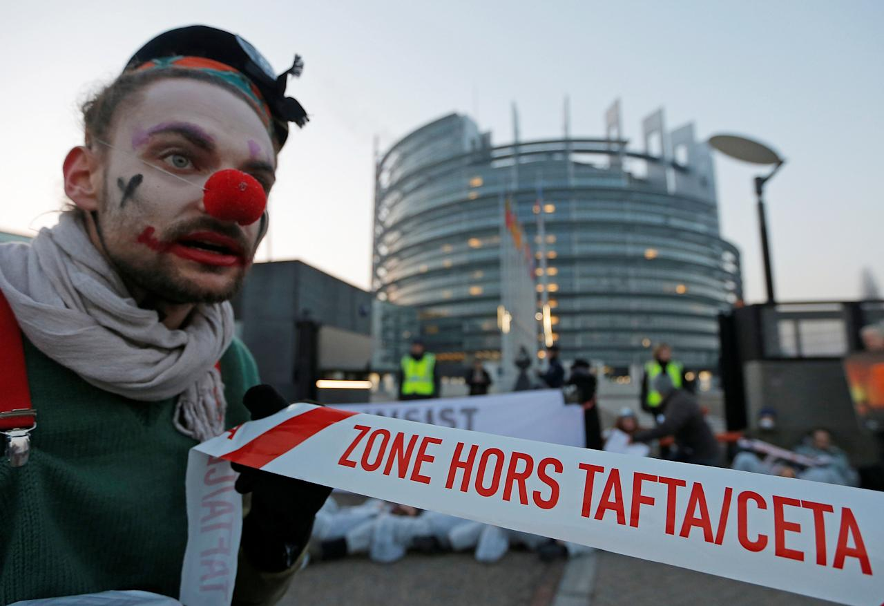 """A demonstrator dressed as a clown holds a banner with the words """"TAFTA/CETA FREE ZONE"""" as he takes part in a protest against the Comprehensive Economic Trade Agreement (CETA) between the EU and Canada, in front of the European Parliament in Strasbourg, France, February 15, 2017.  REUTERS/Vincent Kessler      TPX IMAGES OF THE DAY"""