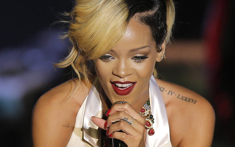 """FILE - In this Wednesday, July 10, 2013 file photo, singer-songwriter Rihanna performs at """"Le Sporting"""" in Monaco during her """"Diamonds World Tour"""" to Europe. Rihanna has left behind a trail of racy tweets and an incriminating Instagram photograph from a Thailand trip that led police to arrest two men for peddling protected primates. (AP Photo/Lionel Cironneau, File)"""