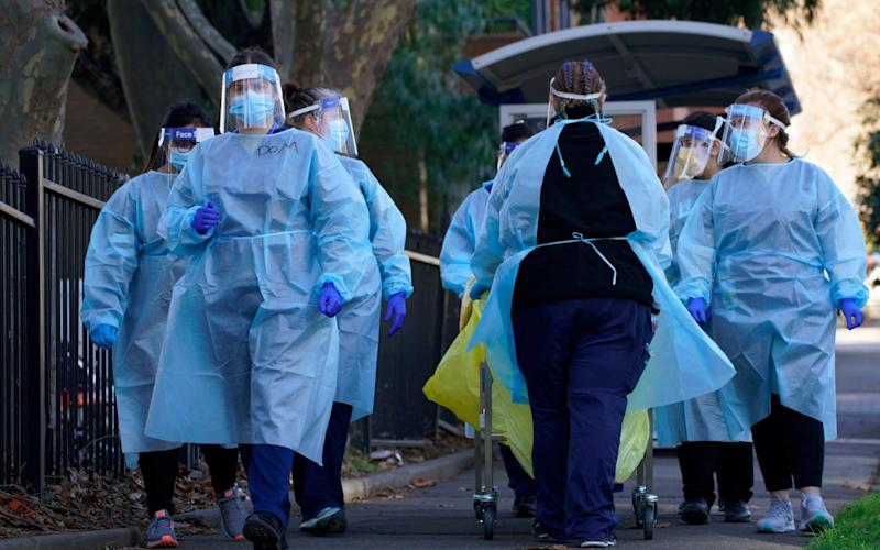 Healthcare workers walk with testing supplies into a public housing tower, locked down in response to an outbreak of the coronavirus disease - Stringer/Reuters
