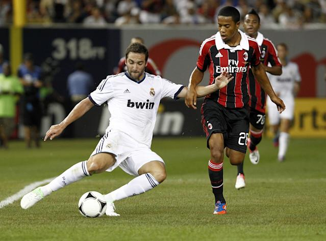 NEW YORK - AUGUST 08: Gonzalo Higuain #20 of Real Madrid clears the ball in front of Urby Emanuelson #28 of A.C. Milan during their match at Yankee Stadium on August 8, 2012 in New York City. (Photo by Jeff Zelevansky/Getty Images)