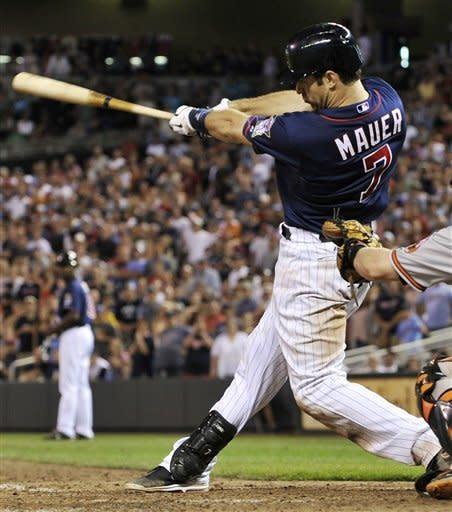 Minnesota Twins' Joe Mauer hits an RBI single off Baltimore Orioles pitcher Pedro Strop in the eighth inning of a baseball game, Tuesday, July 17, 2012, in Minneapolis. Mauer went 3-for-4 as the Twins won 6-4. (AP Photo/Jim Mone)