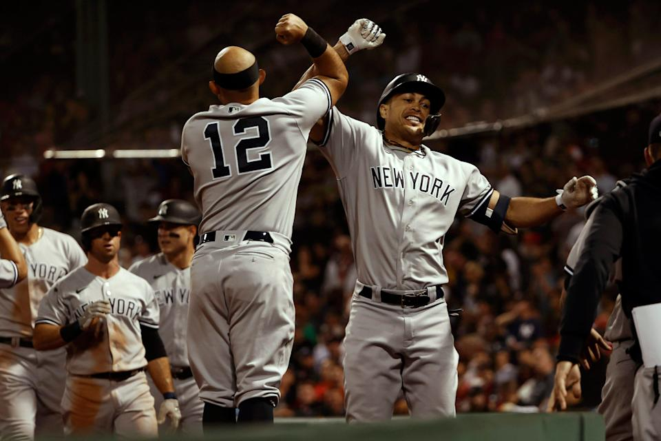 New York Yankees designated hitter Giancarlo Stanton (right) celebrates with second baseman Rougned Odor (left, 12) after hitting a grand slam against the Boston Red Sox during the eighth inning at Fenway Park on Saturday.