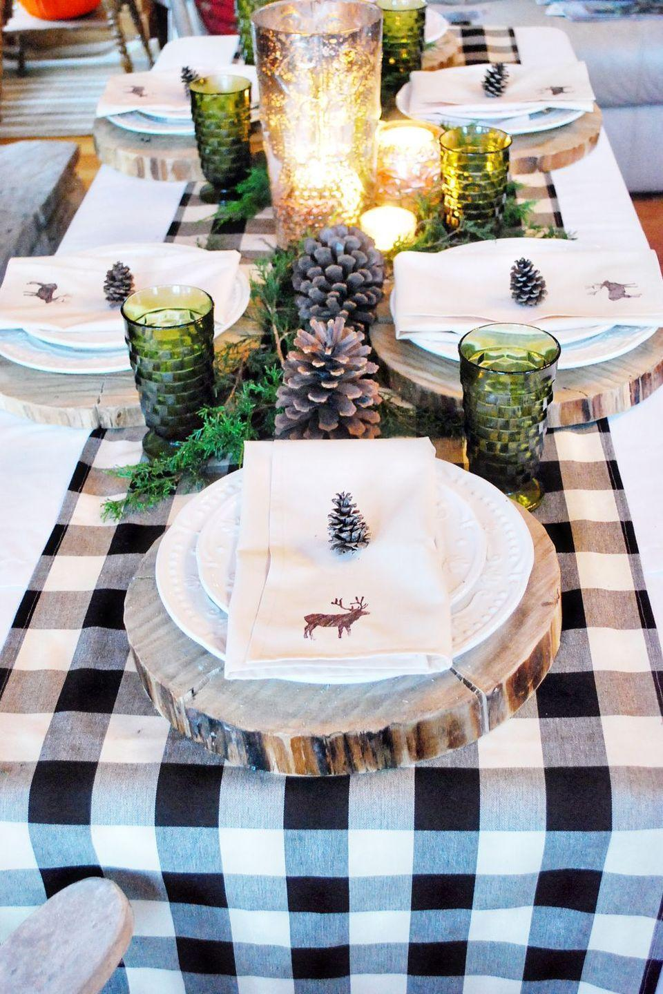 "<p>Fresh greenery, large pine cones, and green-tinted glass make for a stunning, woods-inspired scene. A gingham runner and hand-painted napkins keep things whimsical and fun.</p><p><strong>Get the tutorial at <a href=""http://thewhitebuffalostylingco.com/life-of-splendor-christmas-line/"" rel=""nofollow noopener"" target=""_blank"" data-ylk=""slk:The White Buffalo Styling Co"" class=""link rapid-noclick-resp"">The White Buffalo Styling Co</a>.</strong></p><p><strong><a class=""link rapid-noclick-resp"" href=""https://www.amazon.com/Wilson-Enterprises-Basswood-Excellent-Centerpiece/dp/B06Y5F1K7M?tag=syn-yahoo-20&ascsubtag=%5Bartid%7C10050.g.644%5Bsrc%7Cyahoo-us"" rel=""nofollow noopener"" target=""_blank"" data-ylk=""slk:SHOP WOOD SLICES"">SHOP WOOD SLICES</a><br></strong></p>"