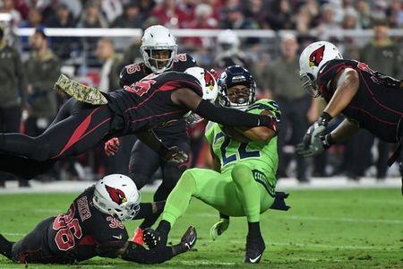 Nov 9, 2017; Glendale, AZ, USA; Seattle Seahawks running back C.J. Prosise (22) is tackled by Arizona Cardinals safety Budda Baker (36), cornerback Tramon Williams (25), linebacker Chandler Jones (55) and defensive tackle Corey Peters (98) during the first half at University of Phoenix Stadium. Matt Kartozian-USA TODAY Sports