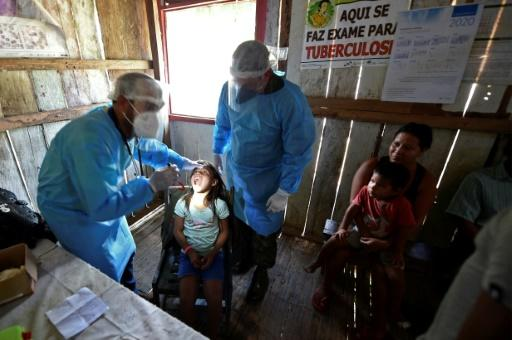 Doctors of the Brazilian Armed Forces check an indigenous child of the Mayoruna ethnic group, in the Cruzeirinho village, near Palmeiras do Javari, Amazonas state, northern Brazil, amid the COVID-19 pandemic