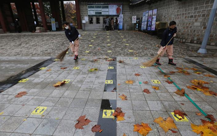 Social distancing signs are seen on the road as people clean fallen leaves in front of the Deoksu Palace in Seoul - AP