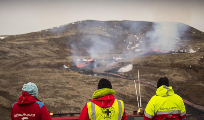 Members of the Search and Rescue Team, Bjorgunasveit look at a new fissure on a volcano on the Reykjanes Peninsula in southwestern Iceland, Monday, April 5, 2021. The new fissure has opened up at the Icelandic volcano that began erupting last month, prompting the evacuation of hundreds of hikers who had come to see the spectacle. Officials say the new fissure is about 500 meters (550 yards) long and about one kilometer (around a half-mile) from the original eruption site in the Geldinga Valley (AP Photo/Marco Di Marco)