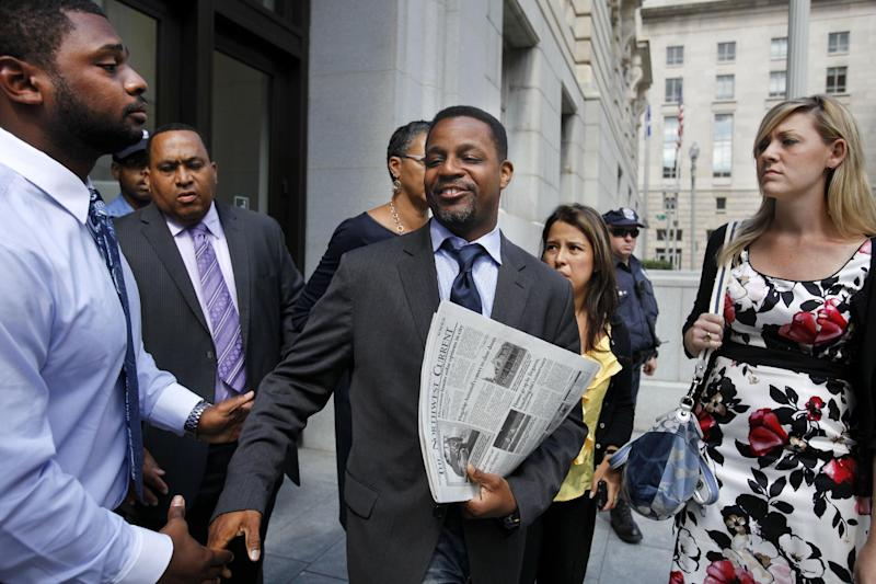 Washington, D.C. City Council Chairman Kwame Brown, center, says goodbye while leaving his office in Washington, Wednesday, June 6, 2012. Brown was charged Wednesday with lying about his income on loan applications, the latest allegation of criminal wrongdoing to roil the local government in the nation's capital. (AP Photo/Jacquelyn Martin)