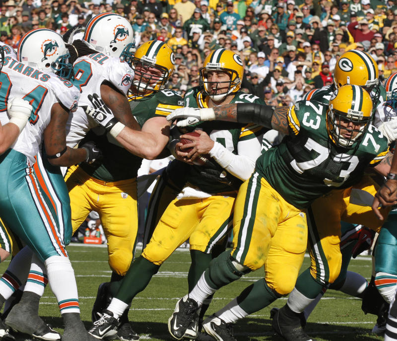 Green Bay Packers quarterback Aaron Rodgers (12) squeezes in for a touchdown against the Miami Dolphins late ino the second half of an NFL football game Sunday, Oct. 17, 2010, in Green Bay, Wis. The Miami Dolphins won 23-20 in overtime. At right is Packers' Daryn Colledge (73). (AP Photo/Jeffrey Phelps)
