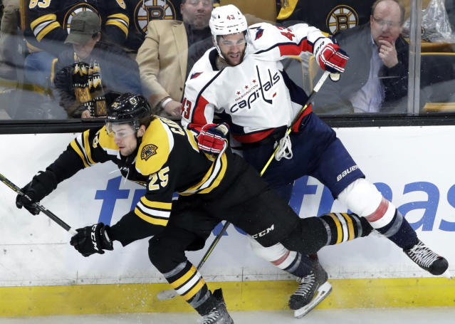 Boston Bruins defenseman Brandon Carlo (25) and Washington Capitals right wing Tom Wilson (43) fight for position along the boards in the third period of an NHL hockey game Thursday, Jan. 10, 2019, in Boston. (AP Photo/Elise Amendola)